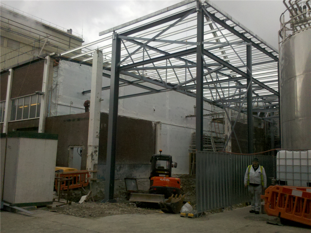 Temporary shrink wrap wall on scaffolding sealed to the building sides and floor during an extension to the production facility. Production continued during the building works. Gallery Image