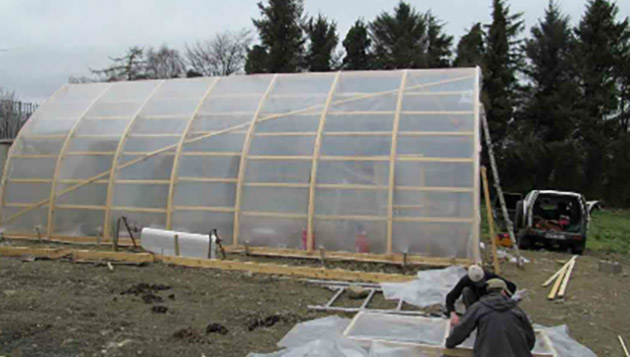 Bow roof shed covered with clear shrink film for use as a greenhouse. We make the bow roof sheds as well! Gallery Image